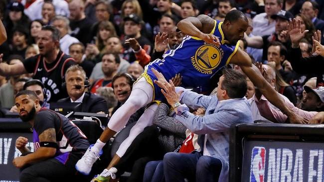 Guard Warriors Andre Iguodala terlempar hingga ke kursi penonton saat tampil di gim 1 final NBA 2019. Iguodala tampil sebagai starter dengan waktu bermain 29 menit 11 detik. (REUTERS/John E. Sokolowski-USA TODAY Sports)