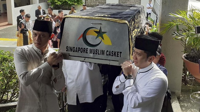 Agus Harimurti Yudhoyono (kiri) dan Edhie Baskoro Yudhoyono memanggul keranda jenazah Ibunda Ani Yudhoyonountuk dimandikan di KBRI Singapura, Sabtu (1/6). Ani telah menjalani perawatan empat bulan di Singapura untuk melawan penyakit kanker darah. (ANTARA FOTO/Naim)