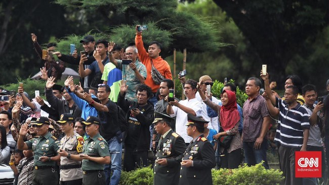 Warga menyaksikan prosesi pemakaman istri mantan presiden ke-enam Susilo Bambang Yudhoyono, Ani Yudhoyono di aman Makam Pahlawan (TMP) Kalibata, Jakarta, Minggu (2/6). (CNN Indonesia/Hesti Rika).