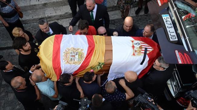 Peti Antonio Reyes yang dibalut bendera desa Utrera and Sevilla FC dimasukkan ke dalam mobil jenazah untuk dibawa ke Gereja Santa Maria de Mesa di Utrera, sebelum dimakamkan. (Photo by CRISTINA QUICLER / AFP)