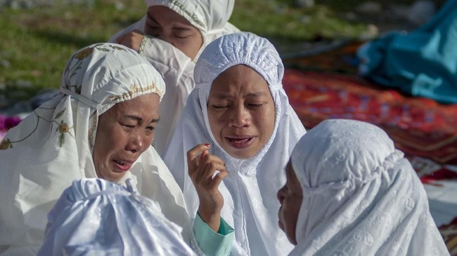 Sejumlah korban bencana terisak dan saling berpelukan usai pelaksanan shalat Id di Kamp Pengungsian Balaroa, Palu, Sulawesi Tengah, Rabu (5/6). Suasana haru meliputi jemaah karena mengenang anggota keluarganya yang telah meninggal akibat bencana 28 September 2018. (ANTARA FOTO/Basri Marzuki)