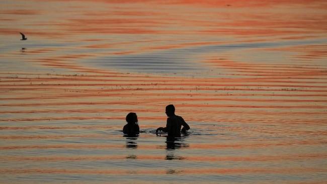 Dua orang menikmati senja di suatu danau di Minsk, Belarusia. (REUTERS/Vasily Fedosenko)