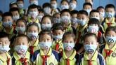 Siswa sekolah dasar mengenakan maskerdengan simbol