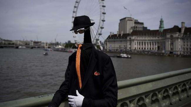 Seorang seniman jalanan berjalan melintasi bianglala London Eye pada suatu hari yang panas di jembatan Westminster di London, Inggris. (REUTERS/Clodagh Kilcoyne)
