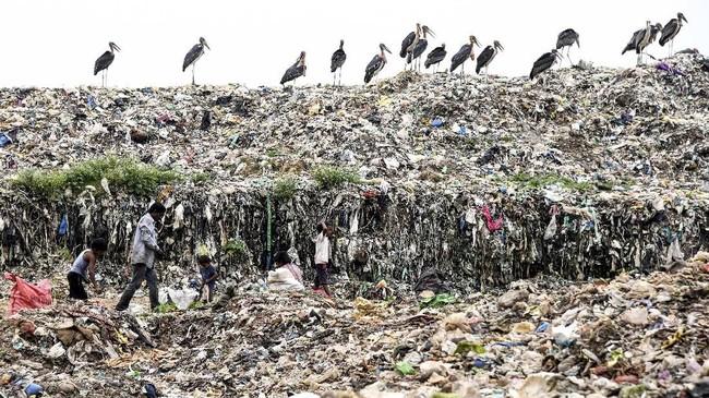 Para pemulung di India mencari benda-benda yang bisa didaur ulang di salah satu tempat pembuangan sampah terbesar di timur laut India dikota Guwahati.(Photo by Biju BORO / AFP)