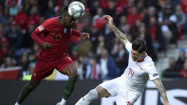 Bek timnas Nelson Semedo menjatuhkan gelandang Swiss Steven Zuber pada menit ke-52. Tapi, wasit Felix Brych tidak memberi Swiss tendanga penalti. (MIGUEL RIOPA / AFP)