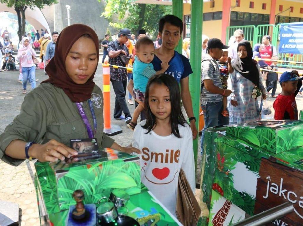 Salah satu pengunjung sedang melakukan tapping JakCard Bank DKI pada mesin antrian masuk Taman Margasatwa Ragunan di Jakarta, Minggu (9/6). Foto: dok. Bank DKI