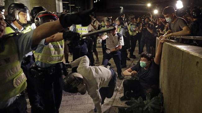 Bentrokan ini mulai terjadi tak lama setelah lewat tengah malam ketika kelompok-kelompok kecil pengunjuk rasa telah merencanakan untuk tetap bertahan di luar kantor parlemen sampai Rabu (12/6). (AP Photo/Vincent Yu)