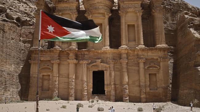 Bendera Yordania berkebar di hadapan biara Nabatean (Ad Deir) di kota kuno Petra di Yordania. Kota yang dibangun ribuan tahun lampau ini merupakan salah satu tujuan paling populer di negara tersebut dan pernah dipilih sebagai salah satu dari tujuh keajaiban dunia pada 2007. (Photo by THOMAS COEX / AFP)