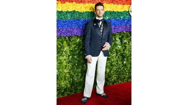 Michael Urie memakai jas berwarna hijau tua yang dipadukan dengan celana panjang putih. Dia memakai rancangan Joseph Abboud untuk Reem Acra. (Dimitrios Kambouris/Getty Images for Tony Awards Productions/AFP)