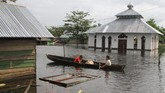 Dua anak berada di atas perahu menerobos banjir sejak dua pekan lalu di Desa Laloika, Kecamatan Pondidaha, Konawe, Sulawesi Tenggara, Minggu (9/6). (ANTARA FOTO/Jojon)