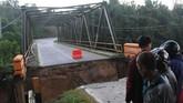 Warga melihat jembatan Ameroro yang menjadi akses jalan trans sulawesi yang rusak akibat banjir bandang di Desa Ameroro, Konawe, Sulawesi Tenggara, Senin (10/6). (ANTARA FOTO/Jojon)