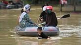 Seorang anak membantu menarik perahu yang disediakan dari Dinas Sosial Dinas Sosial Provinsi Sulawesi Tenggara saat banjir bandang terjadi di pemukiman di Kelurahan Wanggu, Kendari, Sulawesi Tenggara, Senin (10/6). (ANTARA FOTO/Jojon)