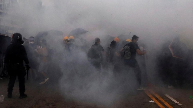 Polisi juga mulai merangsek maju dengan menyingkirkan pagar besi yang semula disusun para demonstran sebagai barikade. (REUTERS/Tyrone Siu)