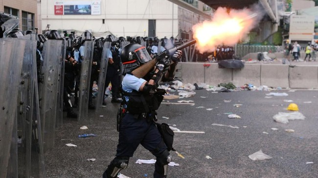 Sebagian masa pengunjuk rasa bertahan dengan menghalau tembakan gas air mata menggunakan payung. (REUTERS/Athit Perawongmetha)