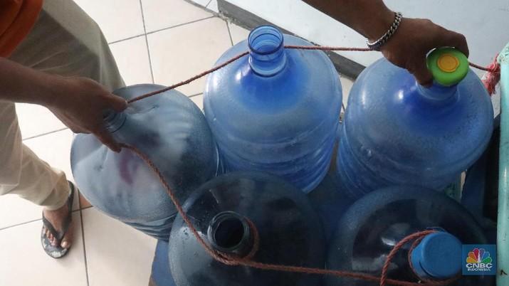 Pedagang air galon membawa galon yang sudah diisi penuh untuk dijual ke warga apartemen di Kawasan Pluit, Jakarta, Rabu (12/6). Banyak penghuni apartemen di kawasan tersebut menggunakan air galon isi ulang untuk mandi. Mumun seorang pembantu rumah tangga mengatakan majiakannya bisa menkonsumsi air galon sehari 4-5 galon untuk mandi dan cuci piring. Harga galon isi ulang ia beli seharga Rp 3500 yang berasal dari air pam, Rp 7000 untuk galon isi ulang untuk galon asli Rp.20.000. Banyak penghuni apartmen menggunakan air galon karena air yang mereka tempati kadang bau dan kotor. (CNBC Indonesia/Muhammad Sabki)