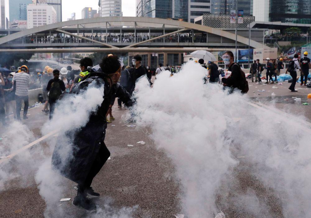 Sejumlah pengunjuk rasa yang terkena gas air mata memilih mundur dan menyelamatkan diri. (REUTERS/Tyrone Siu)