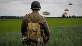 Seorang pria berpakaian sebagai tentara perang melihat ke arah Brigade Udara 16 Inggris dan juga Brigade Perancis yang sedang melompat ke arah Sannerville, barat laut Perancis, sebelum peringatan 75 tahun D-Day, atau ketika sekutu mendarat di Normandy pada Perang Dunia II. (AFP/Guillaume Souvant)