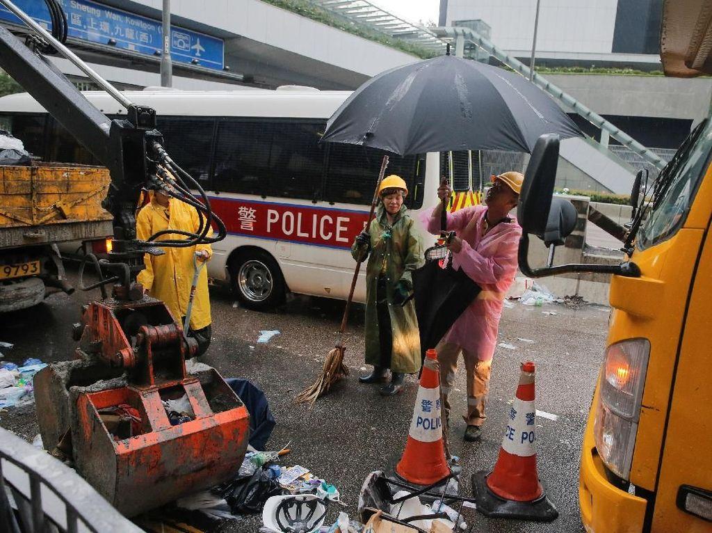 Sejumlah petugas kebersihan menyapu jalan dan mengumpulkan sampah sisa-sisa aksi protes warga terhadap RUU ektradisi beberapa waktu lalu. Thomas Peter/Reuters.