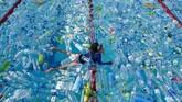 Seorang bocah berenang di suatu kolam yang penuh botol pastik. Ia turut serta dalam aksi mengampanyekan Hari Lautan Sedunia di Bangkok. (AFP/Romeo Gacad)