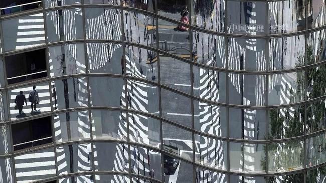 Pada suatu sore yang hangat, bayangan orang-orang yang berjalan di jalur penyebrangan tercermin pada jendela suatu bangunan di Tokyo. (AP/Eugene Hoshiko)