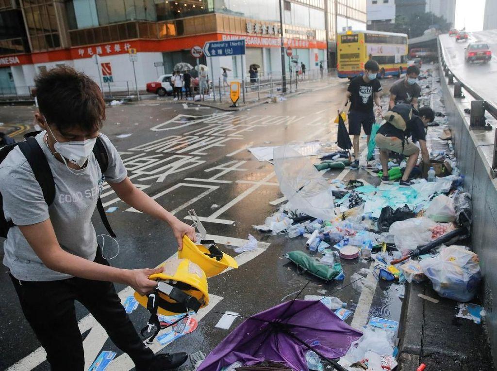 Sejumlah warga Hong Kong nampak membersihkan sampah yang berserakan di jalan usai melakukan aksi protes terhadap Rancangan Undang-undang (RUU) ekstradisi. Thomas Peter/Reuters.