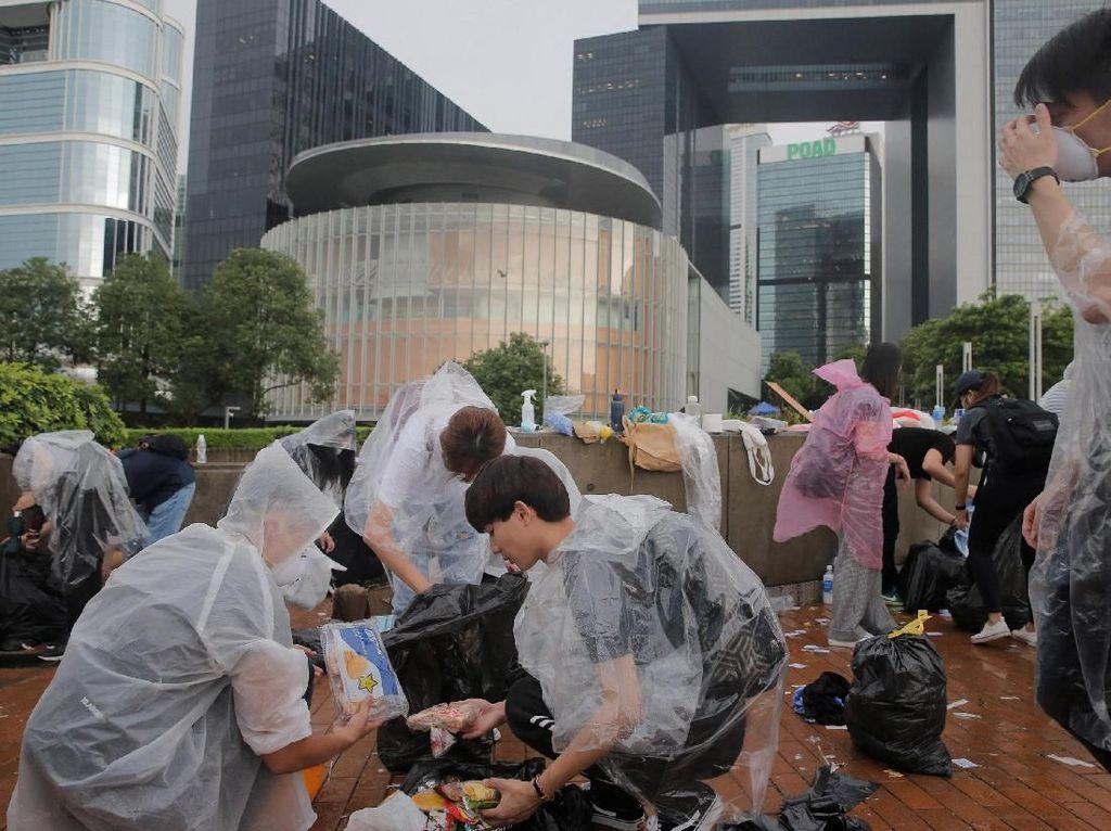 Sambil mengenakan jas hujan untuk mengantisipasi sisa-sisa gas air mata, warga mengumpulkan satu per satu sampah yang berserakan di area sekitar Gedung Legislatif. Thomas Peter/Reuters.