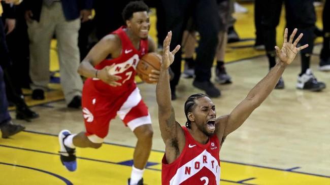 Dua pemain kunci Toronto Raptors, Kawhi Leonard dan Kyle Lowry merayakan kemenangan timnya atas Golden State Warriors sekaligus memastikan gelar juara NBA perdana bagi klub tersebut pada gim keenam final di Oracle Arena, Jumat (14/6). (Sergio Estrada-USA TODAY Sports via Reuters)