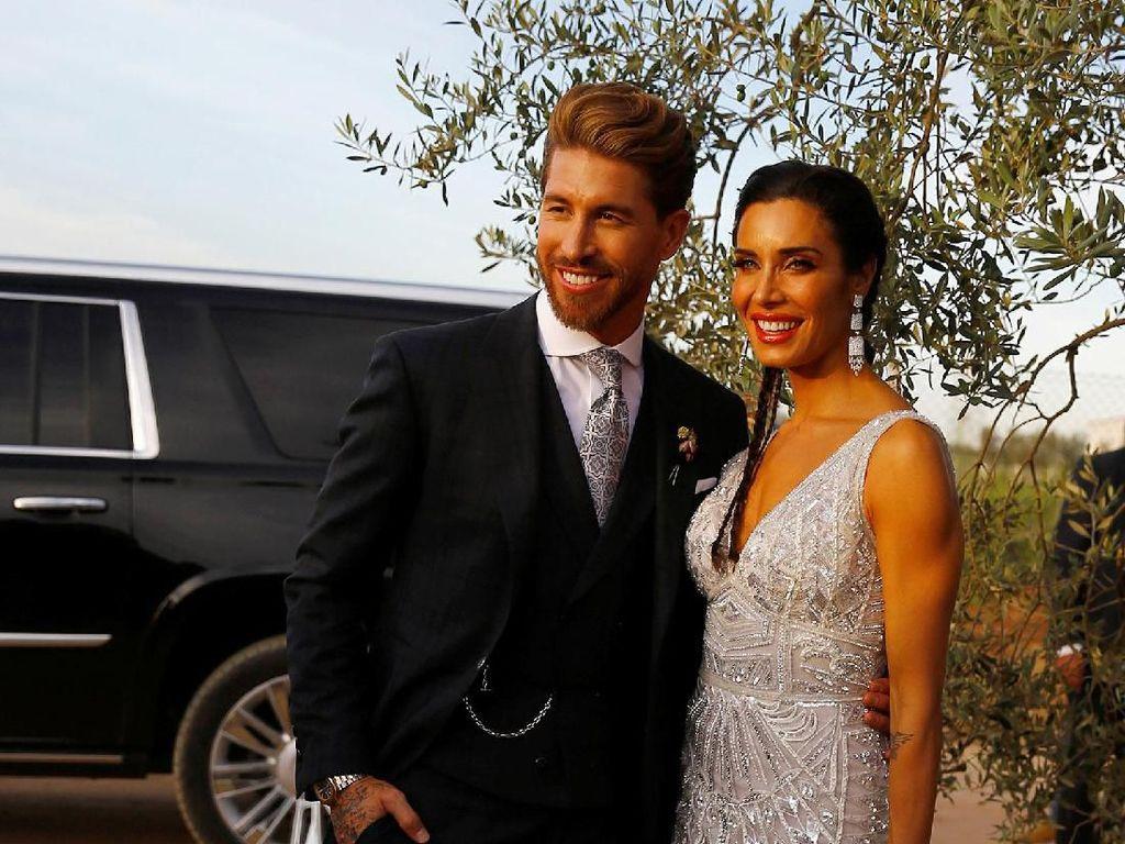 Sergio Ramos melangsungkan pernikahan dengan mengenakan setelan blazer tiga bagian berwarna gelap. Sementara Pilar Rubio mengenakan terusan putih dan membawa buket bunga. Marcelo del Pozo/Reuters.