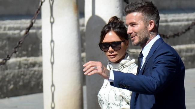 Legenda timnas Inggris dan Real Madrid David Beckham bersama istri, Victoria, menjadi salah satu sosok yang mendapat sambutan meriah di pernikahan Sergio Ramos dan Pilar Rubio. (CRISTINA QUICLER / AFP)