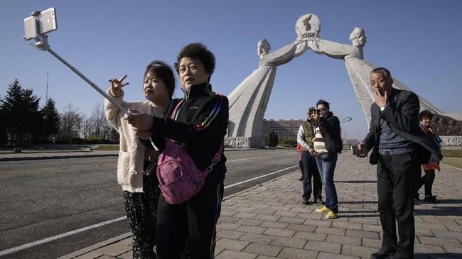 Sekelompok turis asal China berfoto di depan monumen Tiga Piagam (Three Charters) di Pyongyang, Korea Utara. Turis China semakin ramai terlihat di negara pimpinan Kim Jong Un ini.