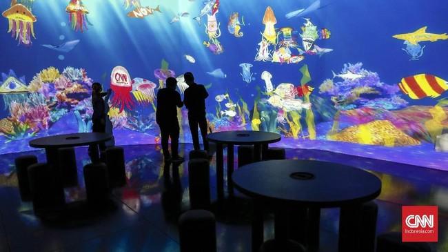 Bayangkan menggambar hewan laut sesuai imajinasi, lalu ia 'hidup' di layar akuarium raksasa. Itu bisa dilakukan di instalasi digital interaktif Sketch Aquarium di 'teamLab Future Park and Animals of Flowers, Symbiotic Lives.' (CNNIndonesia/Safir Makki)