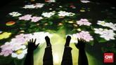 Seni interaktif yang dinamakan lain, Sliding through the Fruit Field, adalah wahana meluncur bagi pengunjung. Saat pengunjung meluncur, cahaya berbentuk buah dan bunga akan ikut menggelinding. (CNNIndonesia/Safir Makki)