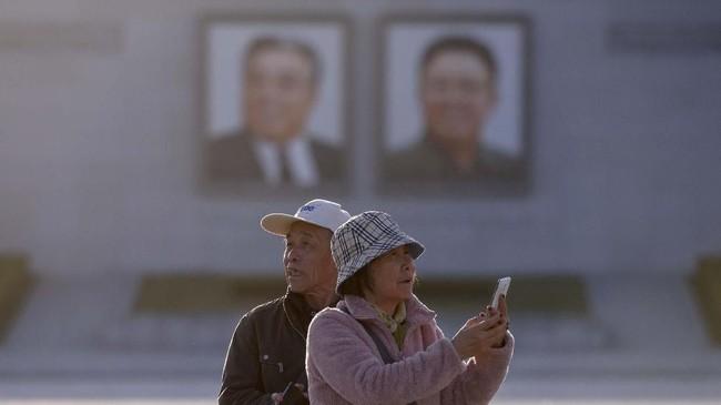 Sepasang turis China berfoto di kawasan alun-alun Kim Il Sung di Pyongyang, Korea Utara. Kesamaan sejarah membuat China dan Korea Utara akur, hingga kini menular ke jumlah kunjungan turisnya.