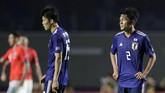 Takehiro Tomiyasu (kiri) dan Daiki Sugioka (kanan) terlihat kecewa usai laga. Kekalahan dari Chile membuat Jepang harus bekerja keras dalam dua laga fase grup selanjutnya menghadapi Uruguay dan Ekuador. (REUTERS/Henry Romero)