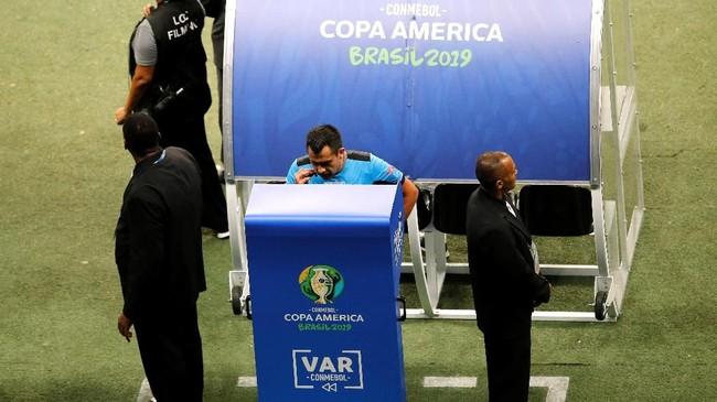Wasit Julio Bascunan asal Chile melihat tayangan ulang sebelum menentukan keputusan. (REUTERS/Luisa Gonzalez)