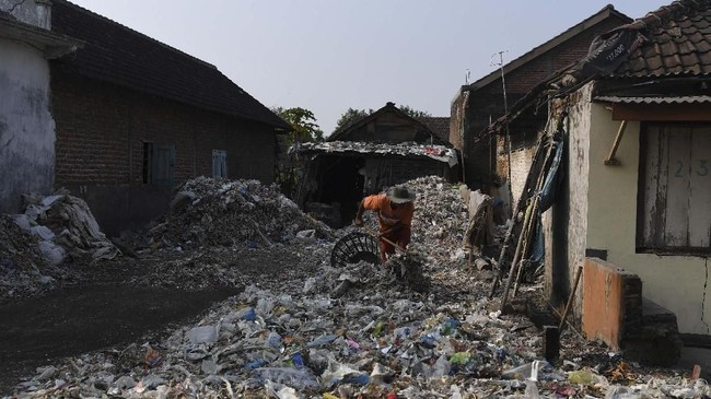 Warga memilah tumpukan sampah plastik impor di halaman rumahnya di Desa Bangun di Mojokerto, Jawa Timur,Rabu (19/6). (ANTARA FOTO/Zabur Karuru)