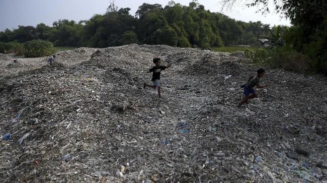 Sejumlah anak berlarian di tumpukan sampah plastik impor di Desa Bangun di Mojokerto, Jawa Timur, Rabu (19/6). (ANTARA FOTO/Zabur Karuru)