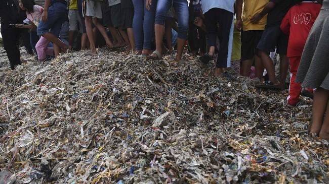 Warga berdiri di atas tumpukan sampah plastik impor di Desa Bangun di Mojokerto, Jawa Timur, Rabu (19/6). (ANTARA FOTO/Zabur Karuru)