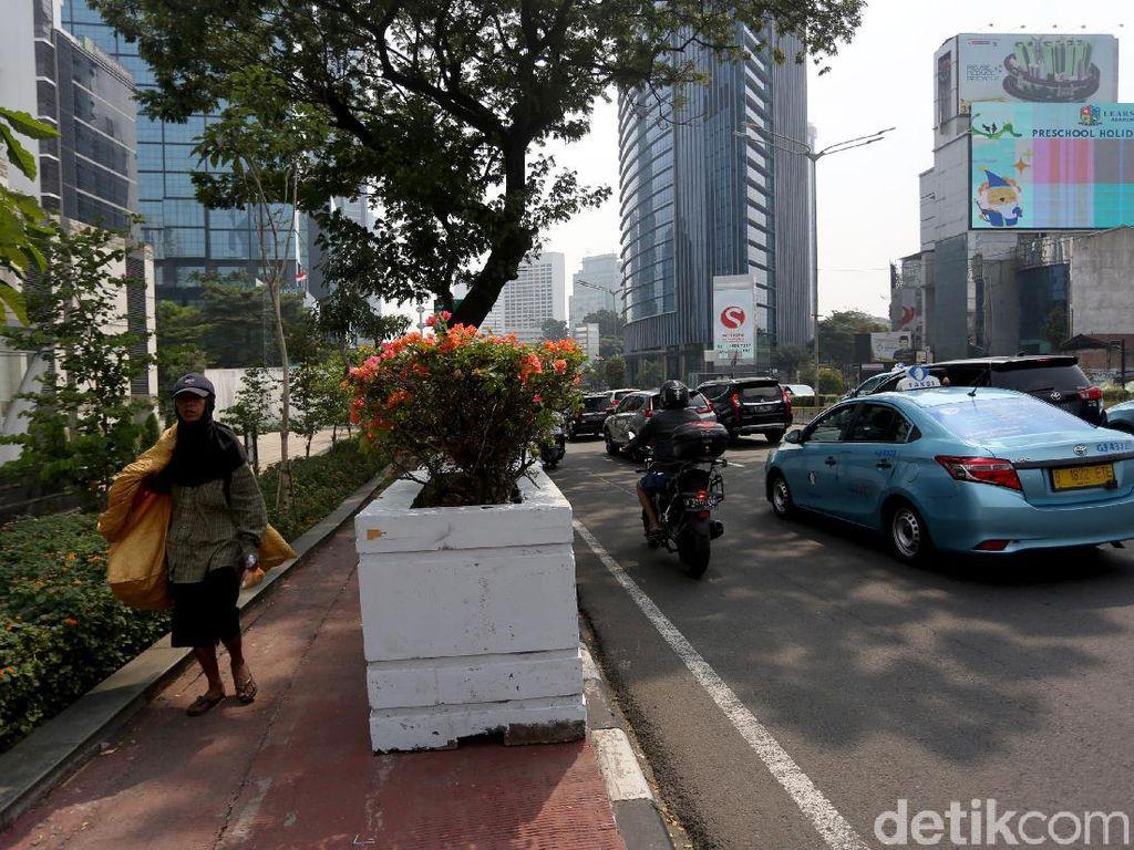 Seorang warga melintasi trotoar yang di sepanjang jalannya dipasangi pot bunga.