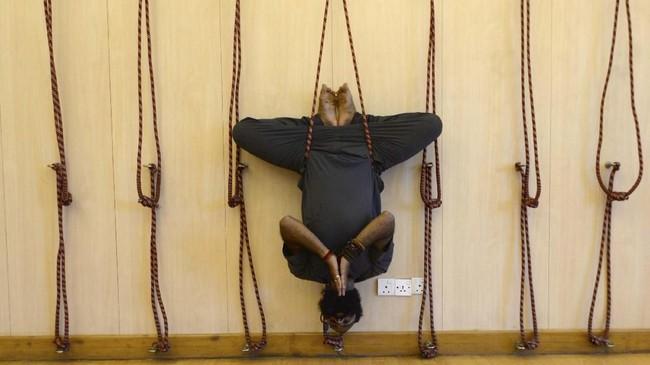Instruktur Ramesh Sapkota, mendemonstrasikan salah satu jenis yoga dalam rangka menyambut Hari Yoga Internasional di Kathmandu, Nepal, Kamis (20/6). (Photo by PRAKASH MATHEMA / AFP)