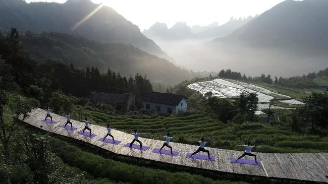 Penggemar berlatih yoga di Desa Qiqi, Zhengjiajie, Hunan, China dalam rangka merayakan Hari Yoga Internasional. (Photo by STR / AFP)