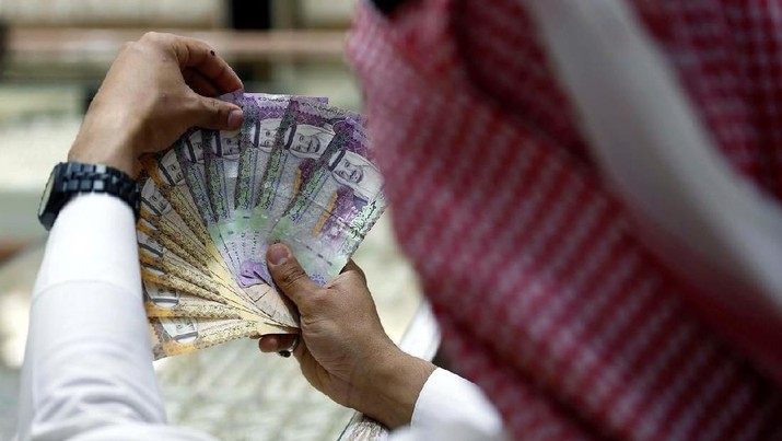 FILE PHOTO: A Saudi money changer displays Saudi Riyal banknotes at a currency exchange shop in Riyadh, Saudi Arabia July 27, 2017. REUTERS/Faisal Al Nasser