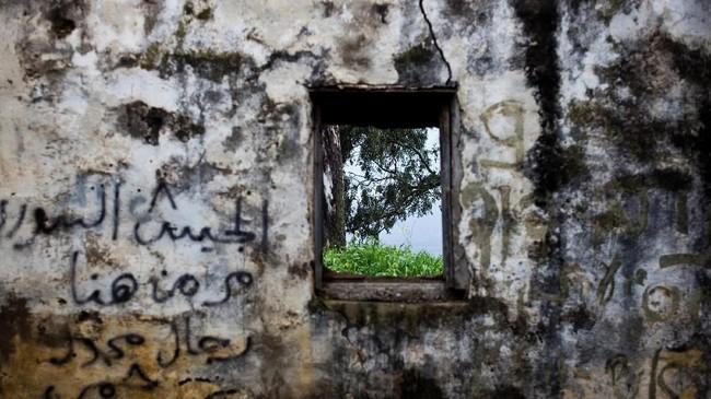 Sisa-sisa pos pantau pasukan Suriah di Dataran Tinggi Golan. Di tembok itu terdapat coretan yang artinya 'Pasukan Suriah pernah ada di sini'. Israel merebut kawasan itu saat berperang dengan Suriah pada 1967. (REUTERS/Ronen Zvulun)