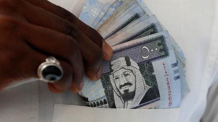 A Saudi man shows Saudi riyal banknotes at a money exchange shop, in Riyadh, Saudi Arabia January 20, 2016. REUTERS/Faisal Al Nasser