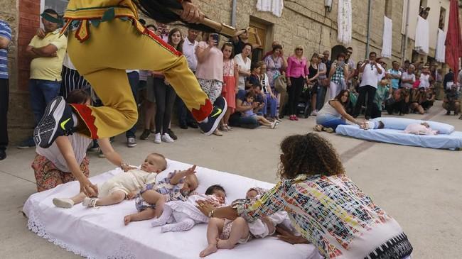 Para bayi yang dilompati tersebut harus berusia 12 bulan setelah dilahirkan, untuk bisa bergabung dalam tradisi El Colacho ini. (CESAR MANSO / AFP)