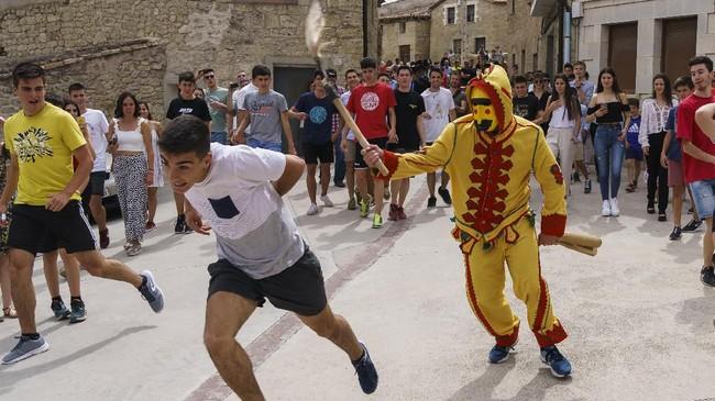 Dalam acara tersebut, seorang pria mengenakan pakaian berwarna merah dan kuning. Pria tersebut melambangkan iblis. (CESAR MANSO / AFP)