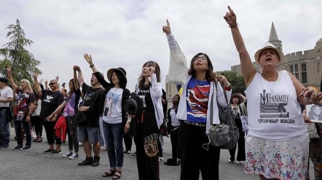 Penggemar serempak menunjuk langit setelah mengheningkan ciptauntuk mengenang Jackson.(REUTERS/Mike Blake)