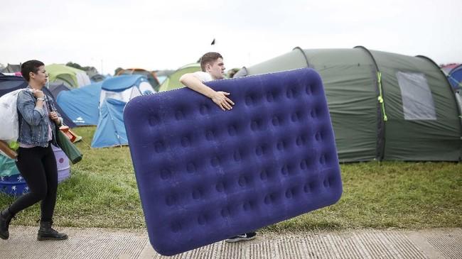Seorang pria rela mengangkat sebuah kasur portabel demi kenyamanan menonton Festival Glastonbury. (REUTERS/Henry Nicholls)