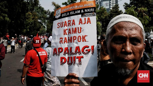 Massa aksi kawal pembacaan putusan sengketa Pilpres oleh MKmenunjukkan poster yang menunjukkan protes mereka atas pelaksanaan pemilu,Jakarta, 27 Juni 2019. (CNN Indonesia/Andry Novelino)